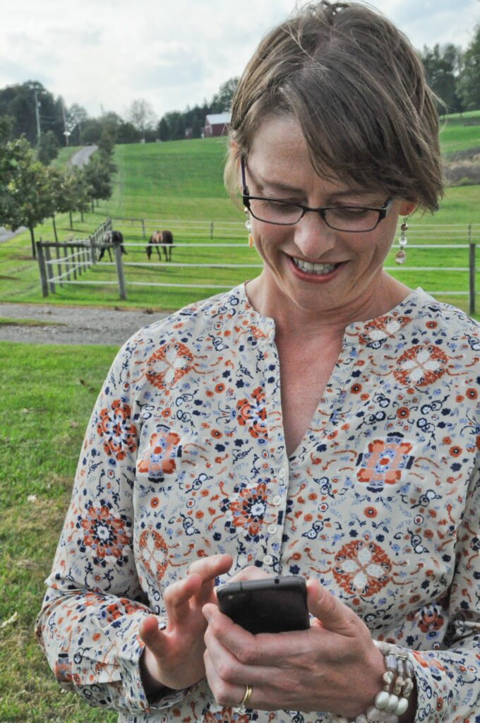 Woman Looking at App on Phone while Horses Graze in Field Behind Her